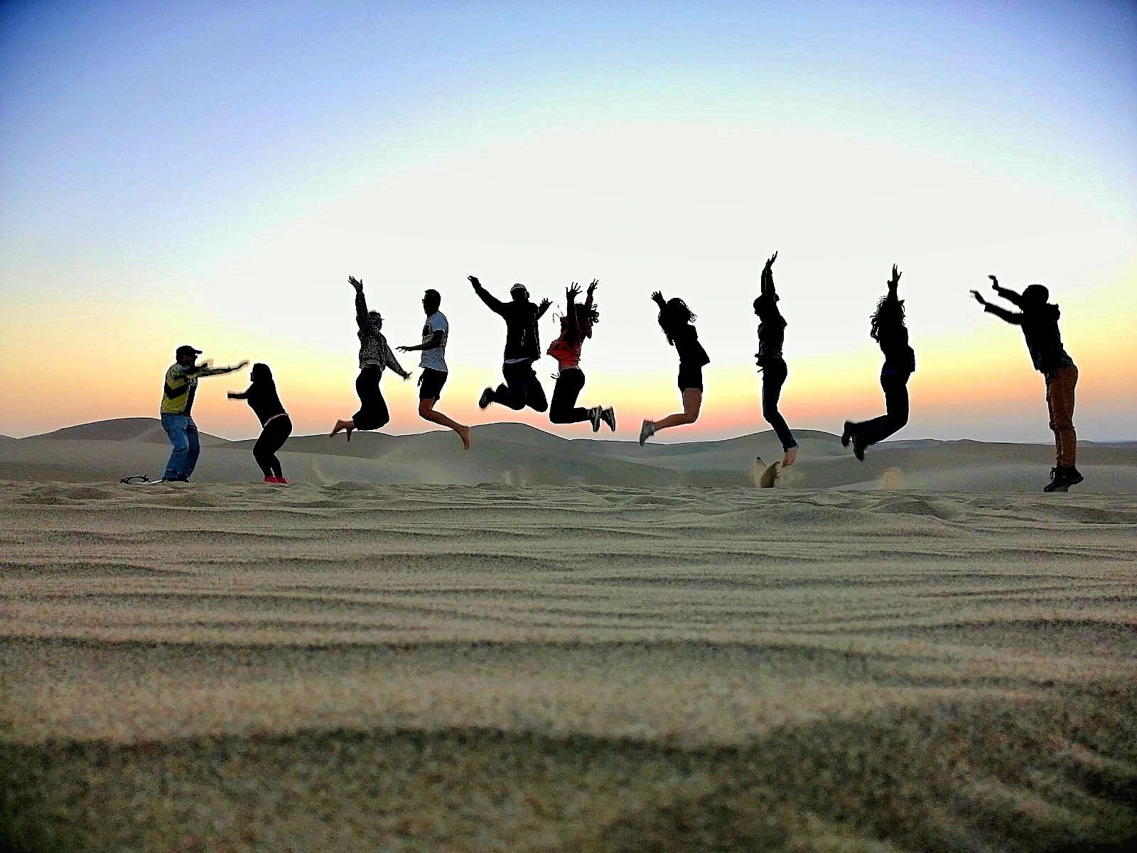 Springen in de woestijn Peru met zonsondergang